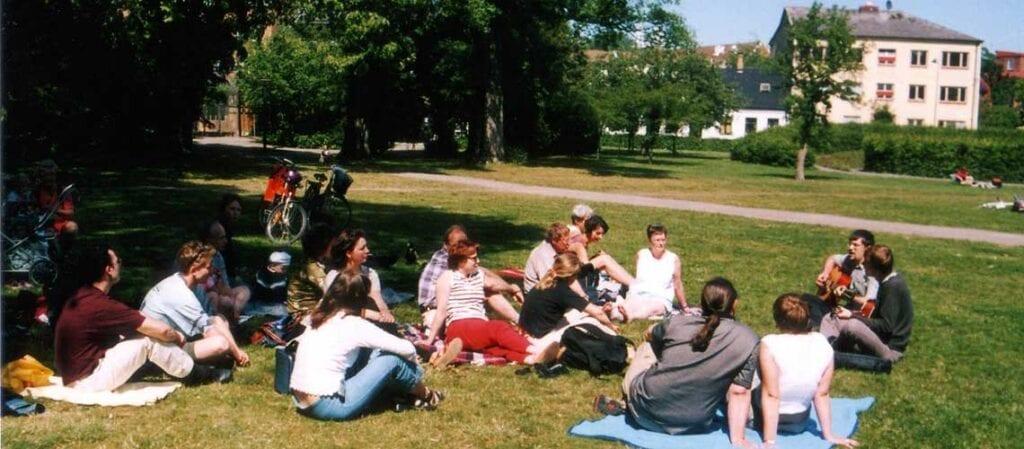människor sittande på gräset i en park