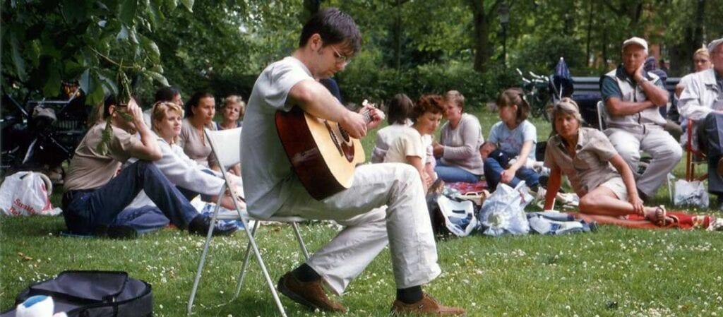 människor sitter på gräset kring en gitarrist som sitter på en stol