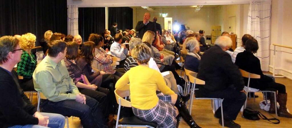 en samling människor som sitter och lyssnar på en talare