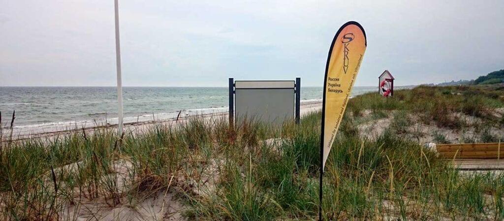 Skruvs gula och orange flagga på en strand med havet i bakgrunden
