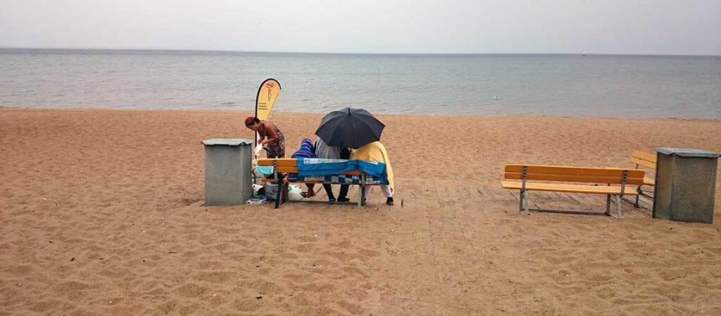 tre personer på en sandstrand
