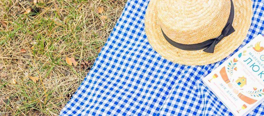 filt på gräset med hatt och bok
