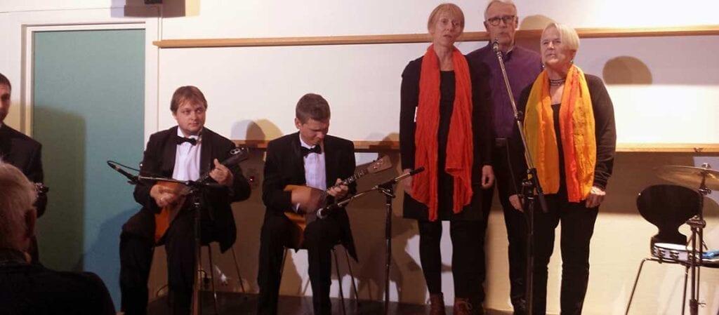 människor som sjunger och spelar balalajka