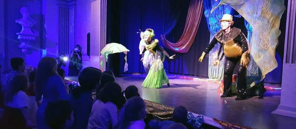 дети на полу смотрят на актеров на сцене