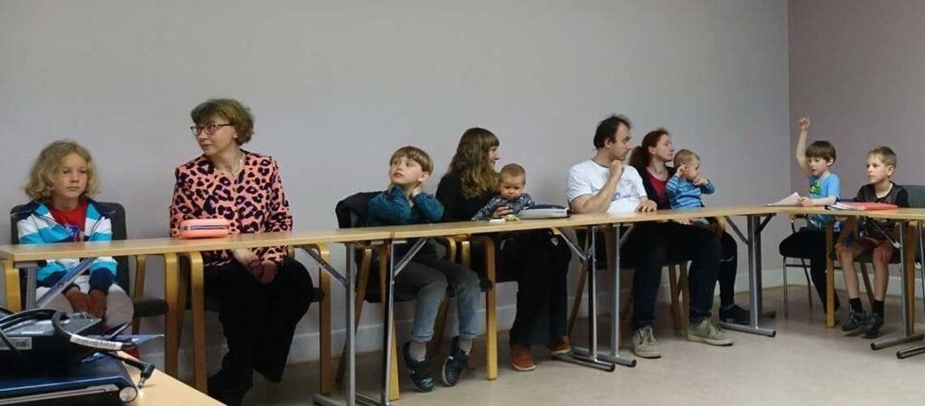 vuxna och barn som sitter vid U-bord