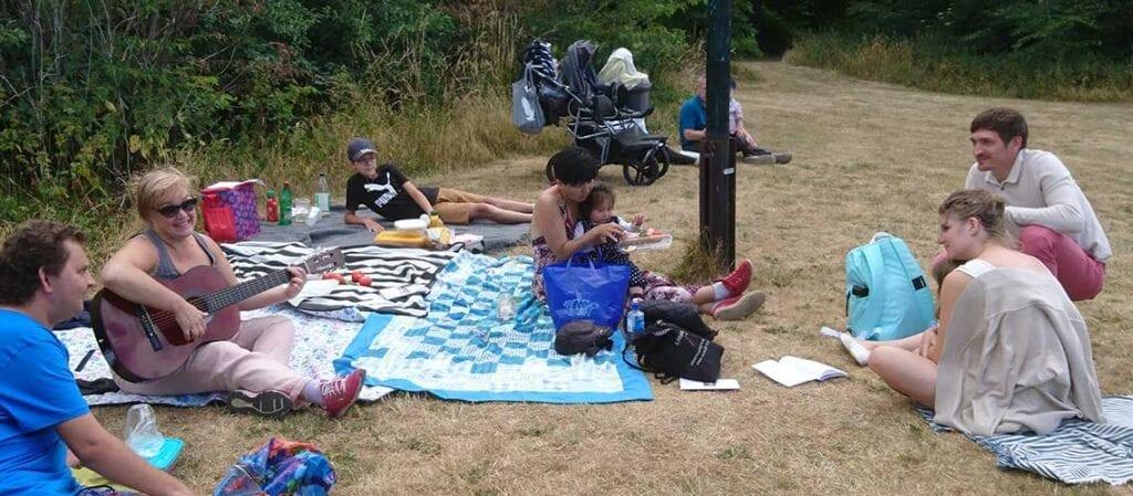 människor som sitter på gräset, kvinna som spelar på gitarr
