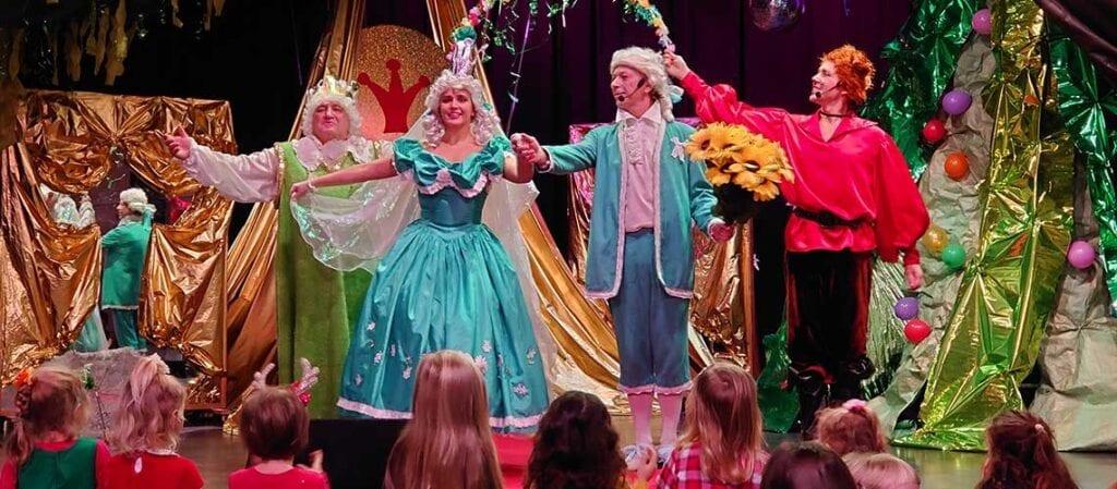 четыре актера на сцене перед детьми, стоящими на полу