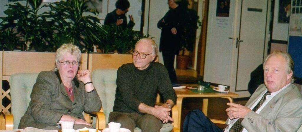 en kvinna och två män sittande kring ett soffbord