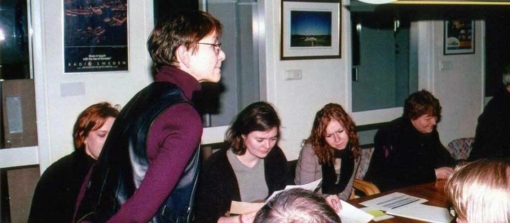 kvinna som står framför människor sittande vid ett bord