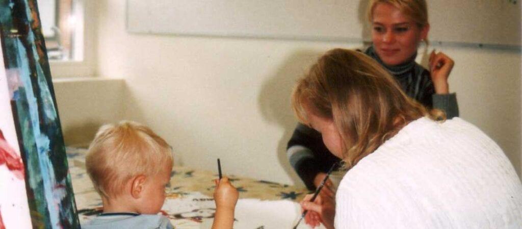 ett målande barn och två vuxna