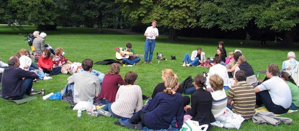 människor som sitter på gräset i en park