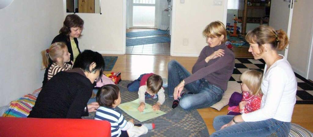 vuxna och barn som sitter i en ring