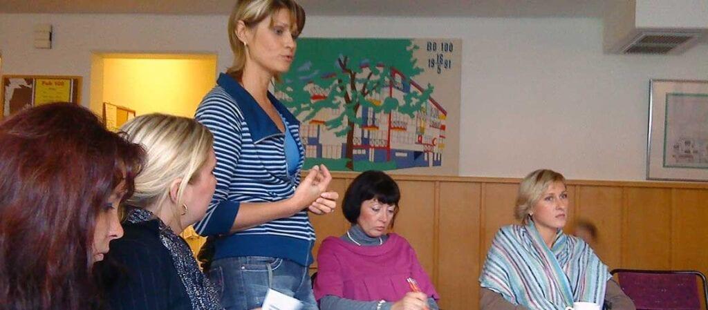 kvinna som står och talar inför sittande kvinnor