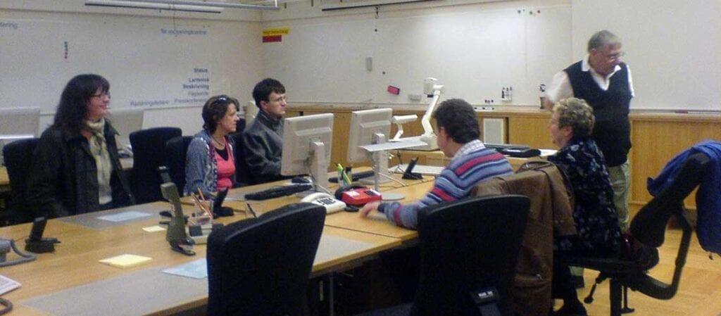 människor samlade kring ett bord framför en föredragshållare