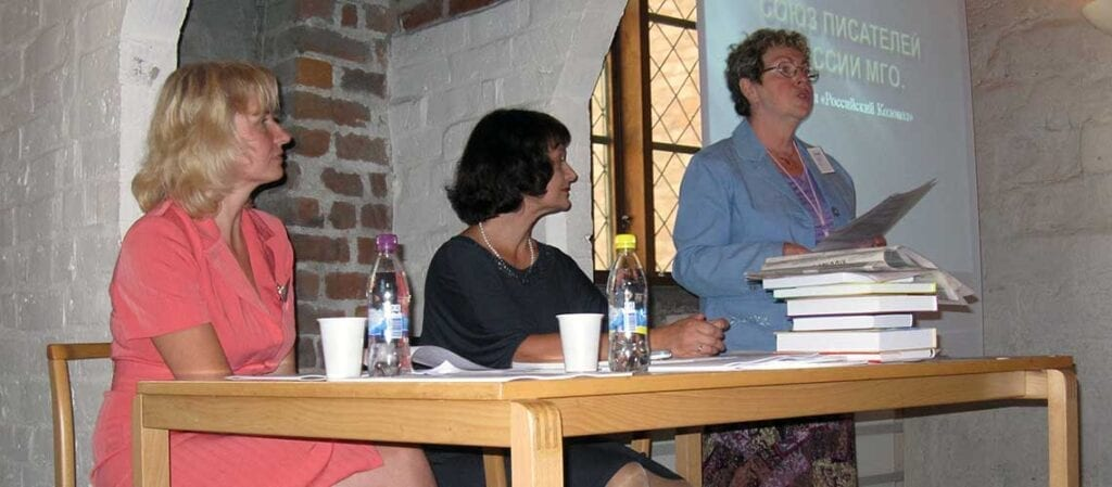 tre kvinnor som talar framför en projektorduk