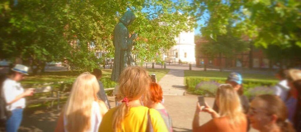 en grupp människor med kameramobiler runt en staty