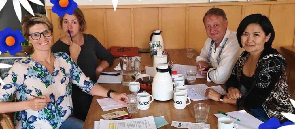 fyra personer i möte vid ett bord