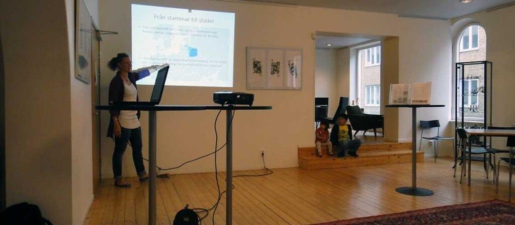 föredragshållare framför projektorbild med text