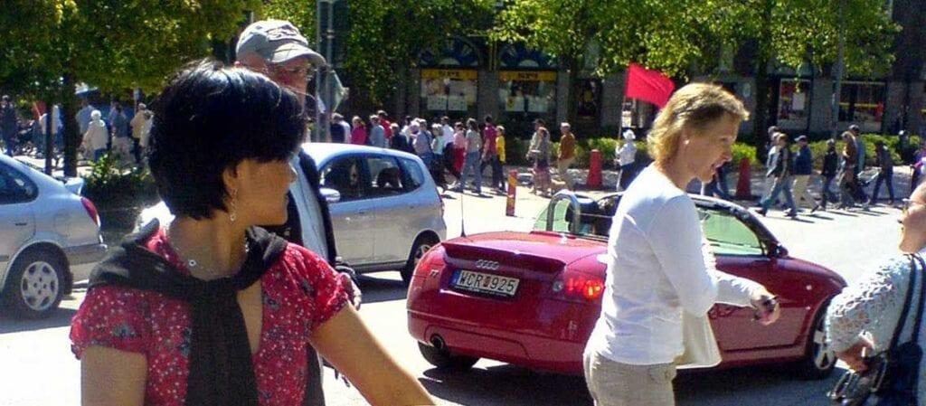 en grupp människor som står och pratar med demonstrationståg i bakgrunden