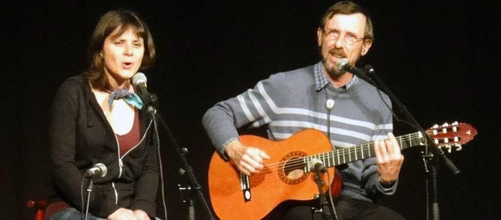 en kvinna som sitter bredvid en man med gitarr