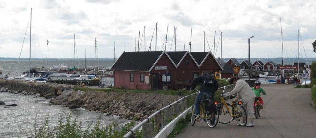 tre cyklister i en hamn