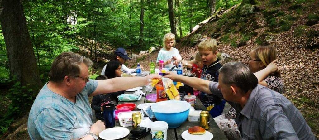 vuxna och barn i skogen vid ett bord med mat
