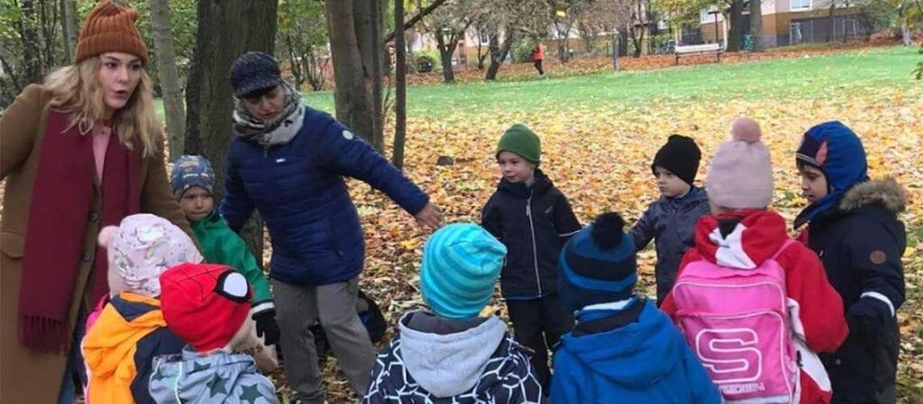 дети и взрослые в хороводе на траве под деревом